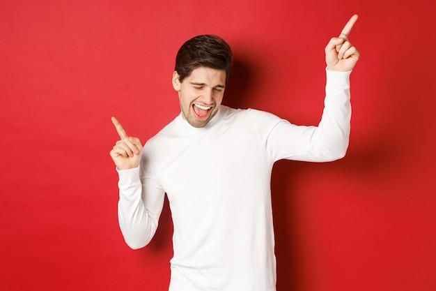 Retrato de homem bonito, aproveitando a festa de ano novo, dançando e se divertindo, apontando os dedos em pé.