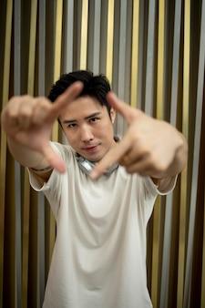 Retrato de homem bonito asiático com fones de ouvido ao ar livre