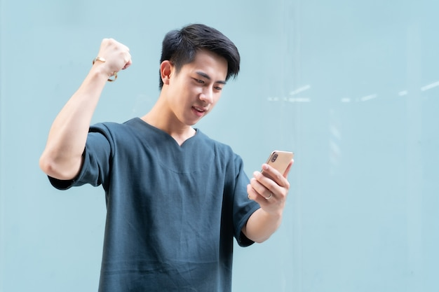 Retrato de homem bonito asiático segurando um smartphone