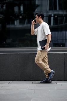 Retrato de homem bonito asiático usando smartphone ao ar livre na cidade