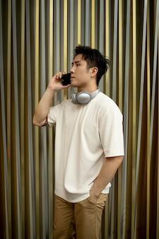 Retrato de homem bonito asiático usando smartphone e fones de ouvido ao ar livre