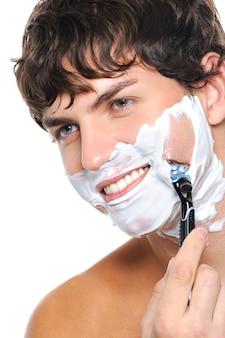 Retrato de homem bonito barbeando o rosto isolado no branco