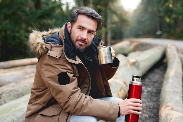 Retrato de homem bonito bebendo chá quente na floresta de outono