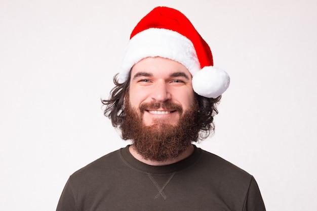 Retrato de homem bonito com barba sorrindo e olhando para a câmera enquanto usava chapéu de papai noel