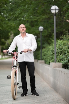 Retrato de homem bonito com bicicleta ao ar livre