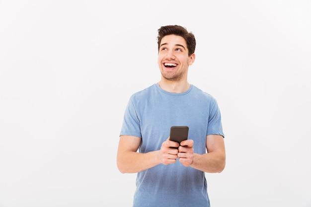 Retrato de homem bonito com cabelo escuro e curto, olhando de lado e sorrindo com celular preto na mão, isolado sobre a parede branca