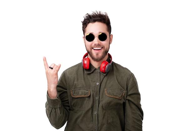 Retrato de homem bonito com óculos escuros e fones de ouvido, fazendo gesto de pedra sobre fundo branco
