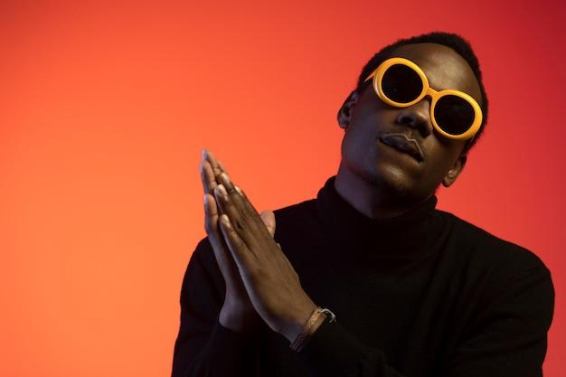 Retrato de homem bonito com óculos escuros sobre fundo laranja