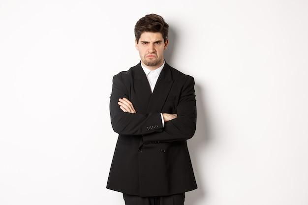 Retrato de homem bonito com raiva em um terno preto, braços cruzados no peito e parecendo ofendido, carrancudo e fazendo beicinho, estando com raiva de alguém, de pé sobre um fundo branco