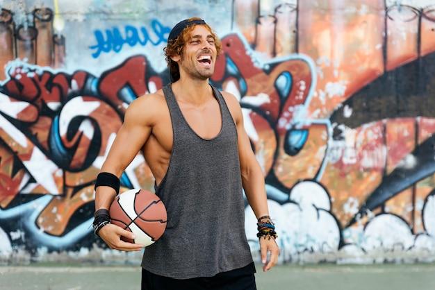 Retrato de homem bonito com roupas esportivas casuais e bola de basquete.
