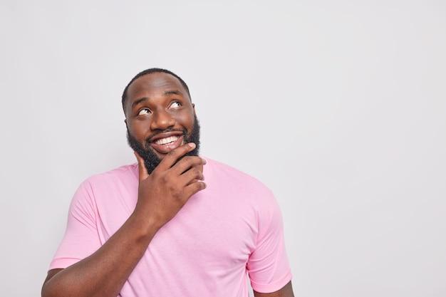 Retrato de homem bonito com sorriso cheio de dentes segurando o queixo focado acima, vestido com uma camiseta rosa casual isolada sobre uma parede branca