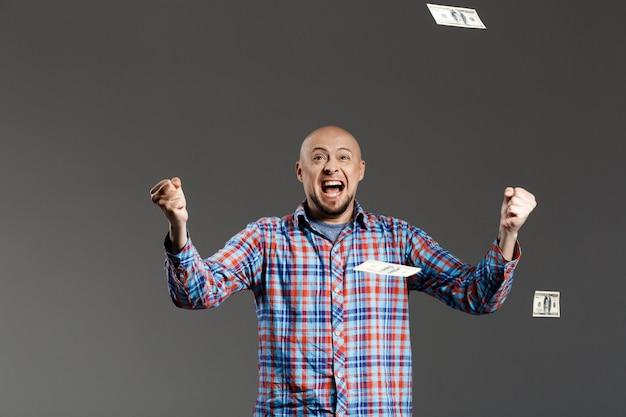 Retrato de homem bonito com sorte na camisa xadrez, agitando as mãos gritando sobre uma parede cinza com dinheiro caindo de cima