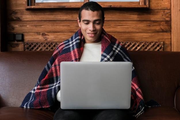 Retrato de homem bonito com um laptop