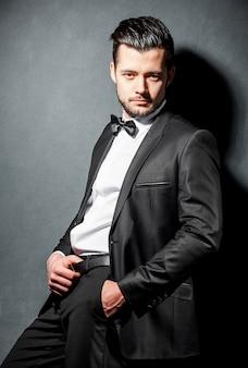 Retrato de homem bonito confiante em terno preto com gravata borboleta