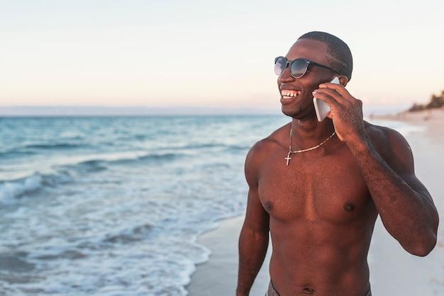 Retrato de homem bonito cubano usando celular na praia.