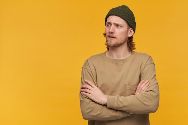 Retrato de homem bonito e adulto com barba e cabelo loiro. usando gorro verde e suéter bege. mantém os braços cruzados. observando à esquerda no espaço da cópia, isole sobre a parede amarela