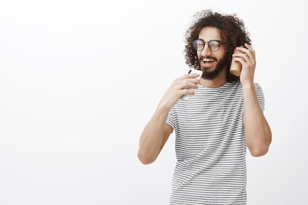 Retrato de homem bonito e despreocupado com barba em óculos escuros, segurando um smartphone como um microfone e cantando junto com uma xícara de café perto do ouvido