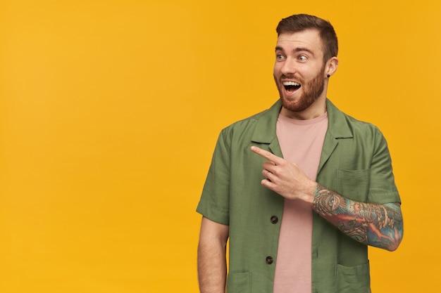Retrato de homem bonito e espantado com barba e cabelo castanho. jaqueta verde de mangas curtas. tem tatuagem. observando e apontando o dedo para a esquerda no espaço da cópia, isolado sobre a parede amarela