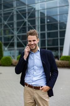 Retrato de homem bonito e sorridente no casual wear, segurando o smartphone. o gerente de sucesso faz uma ligação. jovem empresário falando ao telefone, em pé na rua da cidade, perto do centro de negócios.