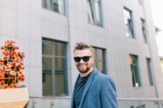 Retrato de homem bonito em óculos de sol, caminhando na rua