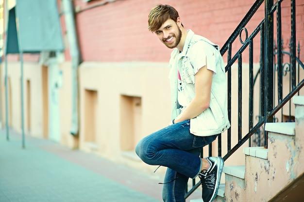 Retrato de homem bonito em roupas elegantes hipster. cara atraente posando na rua