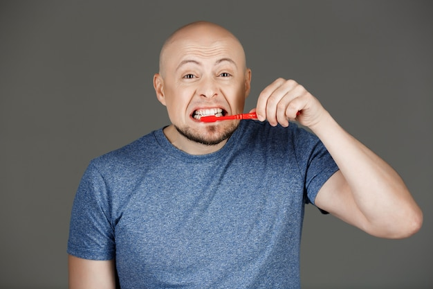Retrato de homem bonito engraçado na camisa cinza, escovar os dentes ao longo da parede escura