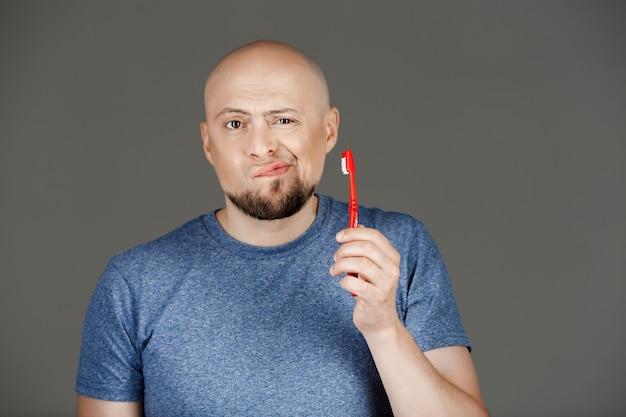 Retrato de homem bonito engraçado na camisa cinza segurando a escova de dentes sobre a parede escura