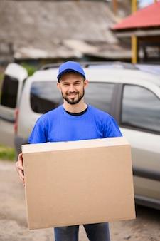 Retrato de homem bonito entrega carregando encomendas
