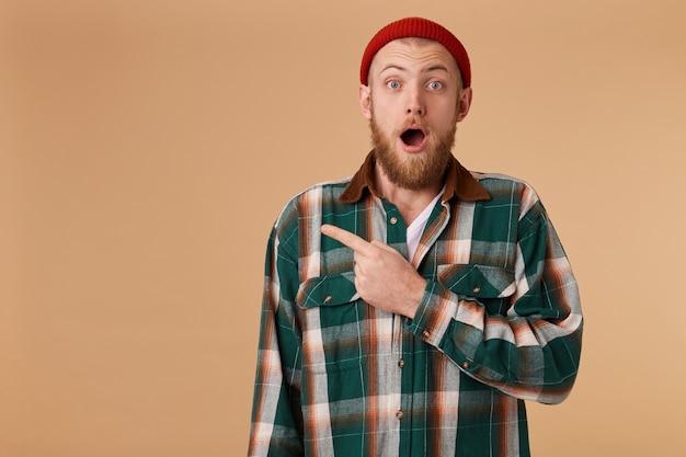 Retrato de homem bonito espantado e impressionado com barba, apontando para o canto esquerdo