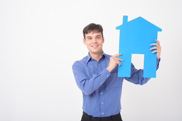 Retrato de homem bonito está segurando papel em casa no fundo branco
