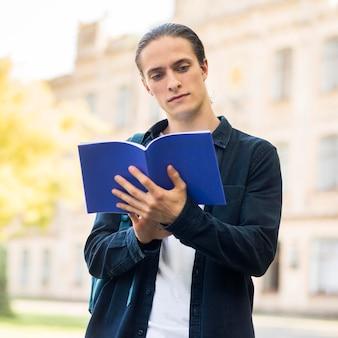 Retrato de homem bonito, estudando no campus