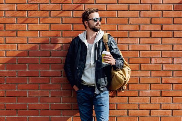 Retrato de homem bonito hippie com barba no chapéu, capuz cinza e jaqueta de couro com mochila segurando uma xícara de café quente
