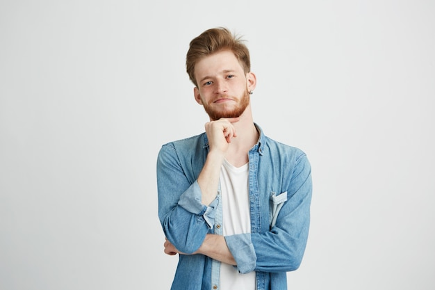 Retrato de homem bonito jovem confiante com barba pensando com mão no queixo.