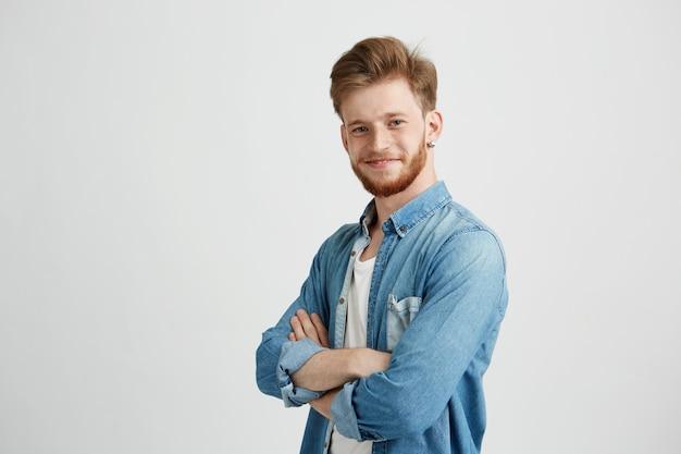Retrato de homem bonito jovem confiante, sorrindo com braços cruzados.