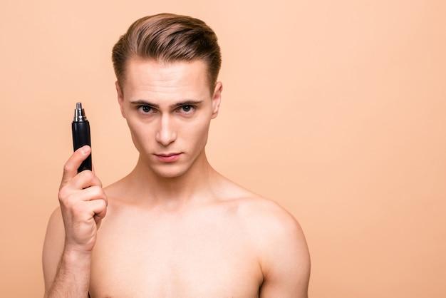 Retrato de homem bonito modelo segurando o aparador remover pelos no nariz ou orelhas isoladas bege