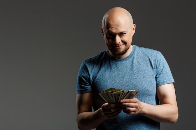 Retrato de homem bonito na camisa cinza, segurando o dinheiro sobre parede escura