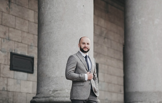Retrato de homem bonito na moda sério em terno posando na cidade