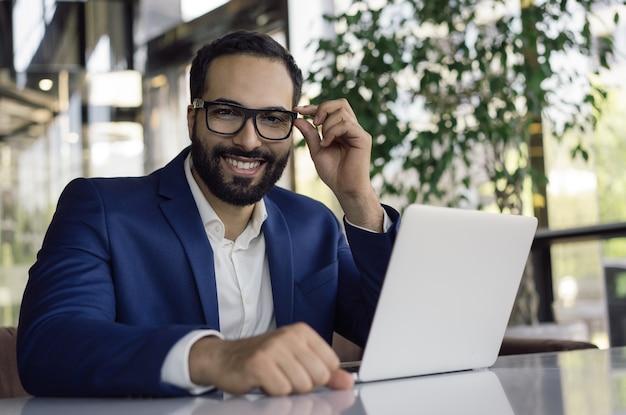 Retrato de homem bonito óculos correto, sentado em um escritório moderno