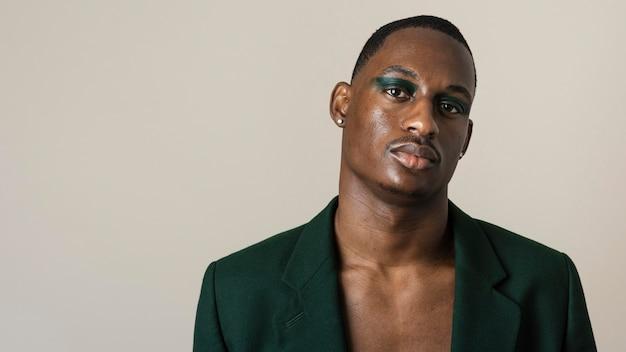 Retrato de homem bonito posando de blazer e usando maquiagem com espaço de cópia