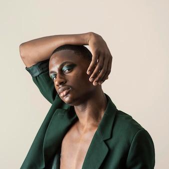Retrato de homem bonito posando de blazer e usando maquiagem