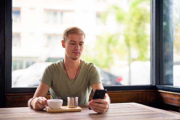 Retrato de homem bonito relaxando na cafeteria