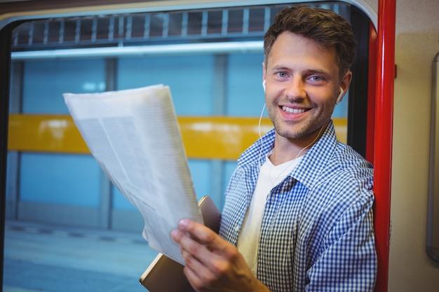 Retrato de homem bonito, segurando o jornal enquanto escuta música
