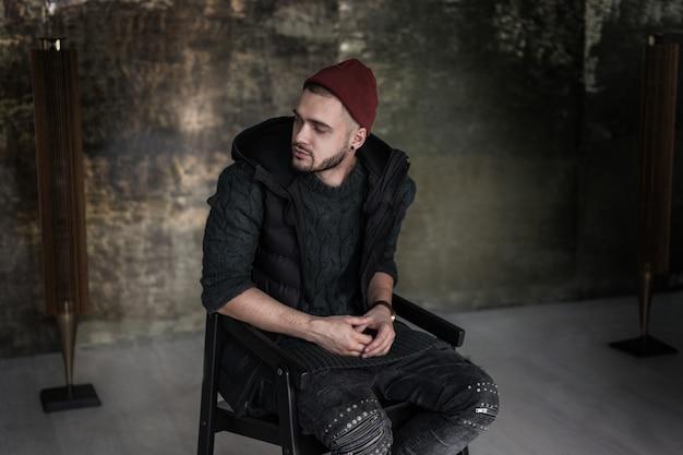 Retrato de homem bonito sentado confortavelmente no sotão de tendência