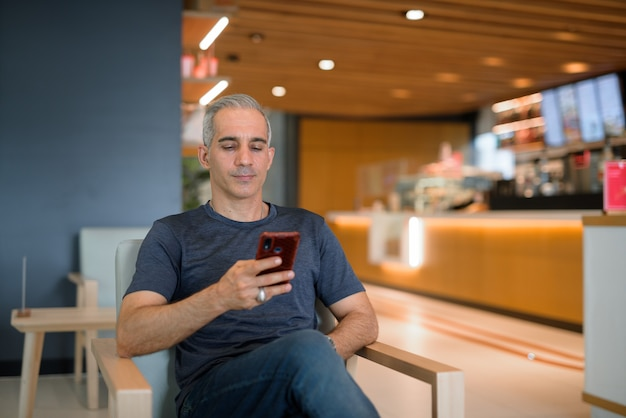 Retrato de homem bonito sentado em uma cafeteria usando foto horizontal de telefone celular