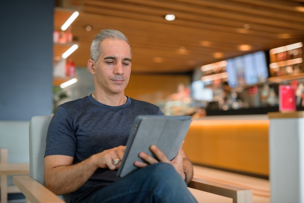 Retrato de homem bonito sentado em uma cafeteria usando tomada horizontal de tablet digital