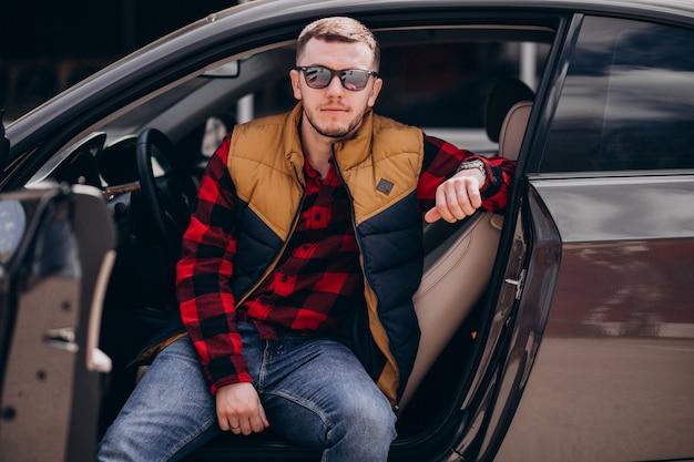 Retrato de homem bonito, sentado no carro