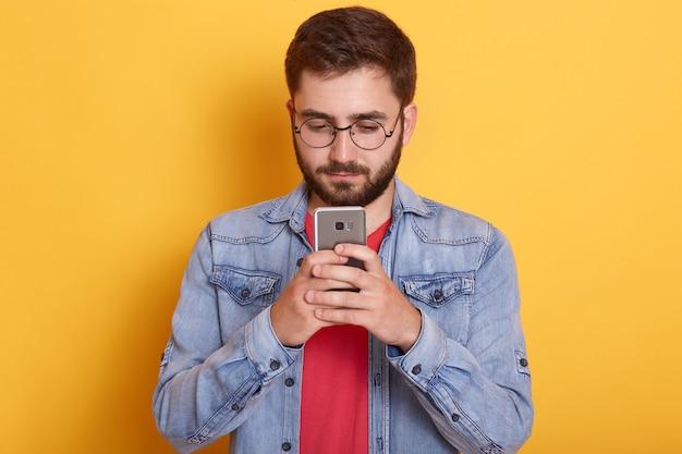 Retrato de homem bonito sério atencioso, segurando seu smartphone nas duas mãos, olhando para a tela, estar interessado no dispositivo