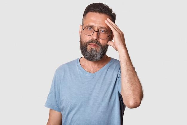 Retrato de homem bonito sério com barba e bigode, mantém a mão na testa, vestindo camiseta cinza
