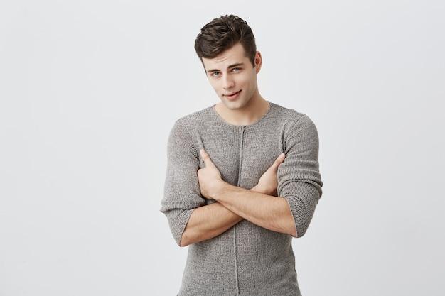 Retrato de homem bonito sério com expressão atraente, mantém os braços cruzados, tenta ser rigoroso. estudante do sexo masculino com ajuste muscular e estilo, insatisfeito com a nota final, exige retomada do exame