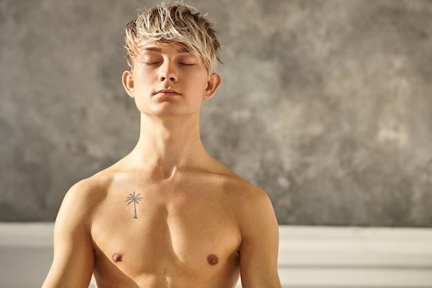 Retrato de homem bonito tatuado praticando ioga dentro de casa, fechando os olhos enquanto medita, tendo uma aparência pacífica, concentrando-se em sua respiração. jovem professor sem camisa fazendo meditação na academia